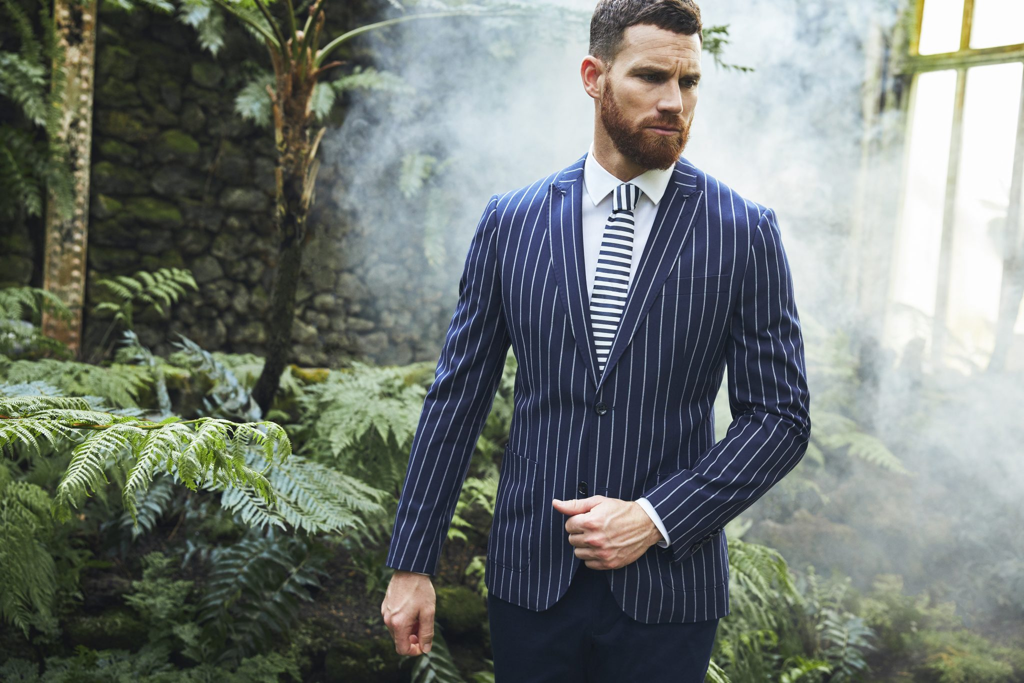 male model wearing a suit in a greenhouse